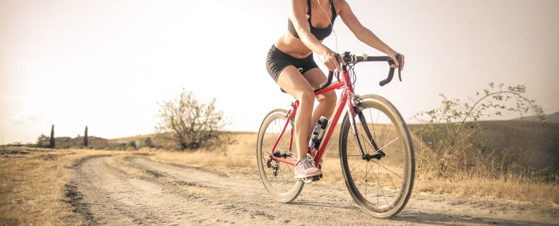 woman-in-black-tank-top-and-black-shorts-riding-red-bicycle-3771834